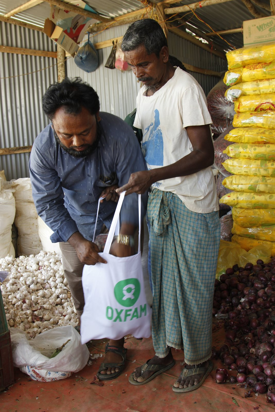 180430_Bangladeshi store keeper MD Ruhulamin packs fresh veges & spices bought with Oxfam cash vouchers for Rohingya refugee Kefayatullah.JPG
